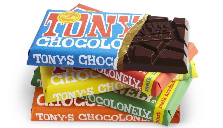 """Tony's Chocolonely, bekend om haar vernieuwende chocoladesmaken en felgekleurde wikkels, streeft naar een wereld met slaafvrije chocolade. Ze willen consumenten bewust maken en concurrenten het goede voorbeeld geven. Een idealistische visie met als fundering een hecht en amicaal team en veel 'fun'. Want zonder plezier ook geen presteren. De cultuur van Tony's samengevat? Hard werken, idealisme, discoballen, schommelstoelen en 'fun along the way'. #1 Het zit wel goed met de 'waarom'-vraag Tony's Chocolonely is opgericht om misstanden in de cacaosector, zoals slavernij en kinderarbeid, tegen te gaan. Omdat je samen nu eenmaal sterk staat, wil Tony's deze visie realiseren door concurrenten het goede voorbeeld te geven en laten zien dat eerlijke chocolade ook commercieel succesvol kan zijn. Vanwege dit idealistische en inspirerende streven, dat wereldwijd succesvol is, ontving CEO Henk-Jan Beltman in 2015 nog de EY Emerging Entrepreneur Of The Year. Beltman vindt ook dat zijn bedrijf, die geen eigen productie heeft, in alles chocolade moet voelen, proeven en ademen. #2 Een chocolademaker die zijn medewerkers gezonder maakt? Het kán. Bij Tony's heerst het geloof dat de kracht van het bedrijf in de mensen zit. De werkdruk is weliswaar hoog, maar er is ruimte om in 'een amicale en luchtige sfeer stoom af te blazen'. Dit betekent naar je werk komen in je comfortabele weekend-outfit, samen de Dam tot Dam loop rennen, filmavondjes en vooral zijn wie je bent. Want rollenspellen daar doen ze niet aan. Ook wordt de fitheid in de gaten gehouden. Elke nieuwe medewerker een paar hardloopschoenen mee naar huis, kan elk jaar €100 aan sportkleding declareren en wordt aan het eind van het jaar op de weegschaal gezet om te kijken of je de """"BMI-bonus"""" hebt gehaald. Deze bonus wordt, net als de niet-roken-bonus, eenmaal per jaar uitgereikt aan werknemers met een structureel gezond gewicht. Dit is ook wel nodig, aangezien je onbeperkt chocolade mag eten. Is het niet gelukt te stoppen met r"""