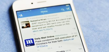 Pittsburgh, USA - February 16, 2015   iPhone 6 displaying Twitter feed including tweets by The Daily Mail and Entertainment Weekly.   The Daily Mail is a British daily tabloid and in this tweet is reporting The Pope denouncing more barbaric acts by the terrorist group ISIS.