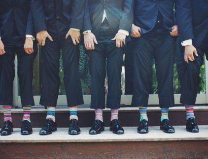 Het dragen van verkeerde sokken kan funest zijn voor je imago. Zelfs als je de mooiste maatpakken draagt word je met verkeerde sokken (denk: witte sportsokken) al snel bestempeld als niet-modieus. Je zou dus kunnen zeggen dat de basis voor een vertrouwelijke outfit ligt bij het dragen van mooie sokken. Fouten met sokken kun je eenvoudig voorkomen. Gelukkig zijn hier ongeschreven regels voor. Helaas zijn deze regels niet bij iedere manager bekend. Daarom hebben we de belangrijkste regels met betrekking tot sokken verzameld. Sokken bij nette kleding Weinig mensen denken bij het opstaan goed na over welke sokken zij aantrekken. Toch zijn sokken een duidelijk zichtbaar onderdeel van je outfit. Vooral bij zakelijke outfits is dit het geval omdat de broekspijpen van pantalons vaak minder lang zijn dan (bijvoorbeeld) broekspijpen van jeans. Om deze reden vallen je sokken hier sneller op. Denk daarom om de volgende tips bij het uitkiezen van sokken bij nette kleding: Zorg ervoor dat je sokken dezelfde kleur zijn als je pantalon of kostuum. Sokken behoren namelijk tot de categorie 'ondergoed' en horen daarom niet op te vallen. Sokken moeten je enkels bedekken. Draag daarom geen enkelsokken onder je pak. Nette sokken (voor onder een kostuum) zijn op de juiste maat als ze tot minimaal de helft van je kuiten komen. Kies voor sokken met voldoende stretch, zodat ze halverwege de dag niet afzakken. Probeer mooie en nette sokken te dragen, ook al zitten je sportsokken nóg zo lekker. Je zult met sportsokken namelijk snel een modeflater slaan. Draag je graag loafers? In de regel draag je deze schoenen zonder sokken. Als je dan toch liever sokken draagt, is het verstandig om enkelsokken te dragen. Op deze manier zijn je sokken minimaal zichtbaar. Wil je toch liever wat meer opvallen met je sokken? Kies dan voor sokken met een patroon. Draag je bijvoorbeeld een blauw pak? Kies dan voor blauwe sokken met een gekleurd patroon. Sokken bij casual kleding Heeft je bedrijf een informele bedr