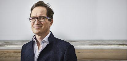 Peter Hinssen (1963) is van huis uit ingenieur en maakte naam als technologieondernemer. Zijn eerste bedrijf E-Com (1995), gespecialiseerd in het bouwen van intranetten, verkocht hij in 1998 aan Alcatel. Daarna volgden succesvolle exits met een bedrijf in videostreaming en een cloudprovider. De laatste jaren is Hinssen actief als consultant, spreker, start-upcoach en docent aan diverse business schools. MT spreekt Hinssen vlak voor het verschijnen van zijn boek, The Day After Tomorrow. Op Schiphol. Hij is onderweg naar Microsoft, om daarna meteen door te vliegen naar het MIT in Boston. Plekken waar termen als Artificial Intelligence, blockchain en kwantumcomputer geen schrikreactie opwekken. Bij de meeste bedrijven gebeurt dat wel, en dat is waarom Hinssen zijn boek schreef. Toekomst In feit is het een vervolg op zijn eerder boek The Normal, waarin hij al heel duidelijk had gemaakt dat de wereld behoorlijk ging veranderen. In dit boek wil hij bedrijven laten zien hoe je op die veranderingen kunt reageren. De truc is vooral tijd inruimen om naar voren te kijken. Hinssen: 'De meeste mensen kijken naar morgen met wat ze van vandaag weten. Ze extrapoleren en denken dan te weten hoe het zal zijn. Maar dan zie je de grote dingen absoluut niet. ' Hinssen ziet dat de een na de andere branche te maken krijgt met disruptie. 'Het is bijna als een soort weerkaart waarop je het ene neerslagfront na het andere ziet naderen. Tien jaar geleden waren de media aan de beurt, de afgelopen jaren de auto-industrie.' De meeste mensen kijken naar morgen met wat ze vandaag weten Op dit moment breekt verzekeraars het klamme zweet uit vanwege de opkomst van Blockchaintechnologie (lees: Wat je moet weten over blockchain). 'Drie jaar geleden huurden de verzekeraars mij nog in als corporate entertainment. Vonden ze mooi als ik vertelde wat er met de banken ging gebeuren. Veel gegniffel, want het ging niet over hen. Maar nu merk je dat die verzekeraars wakker worden: f*ck, we're next', zegt Hinss