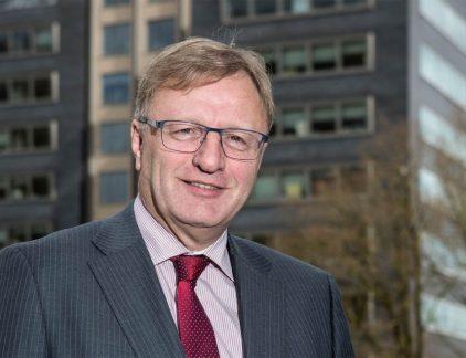 Ruud Majenburg, directeur van de infradivisie van bouwbedrijf Heijmans, vertrekt na 1,5 jaar alweer uit de Raad van Bestuur. Hij is de derde topman in één jaar tijd. CEO Ton Hillen neem tot die tijd zijn taken waar. Een profiel. De aanstelling van CEO Ton Hillen was een onverwachte: krap twee weken nadat CFO Maarten van den Biggelaar de handdoek in de ring gooide, gaf CEO Bert van der Elst te kennen ermee te stoppen. Hillen - sinds 2012 lid van de Raad van Bestuur - schoof door tot voorzitter. Het eerste nieuws dat hij naar buiten bracht was alles behalve positief: een verlies van 110 miljoen euro, een record. Bij de pakken neerzitten deed Hillen echter niet, iets wat hij leerde uit zijn tijd als rallyrijder: samen met Bert de Jong werd hij in de jaren 90 tweemaal Nederlands kampioen. 'Er is altijd weer een dag waarop je verder moet. Bij winst en teleurstellingen,' aldus Hillen in het FD. Financiële problemen Die teleurstellingen, dat zijn er nogal wat het afgelopen jaar bij Heijmans. Door een paar grote projecten raakte het bedrijf financieel in de problemen afgelopen jaar, ondanks dat de bouwmarkt langzaam weer aantrok. Onder andere de N23 en een Energielab dat niet naar wens van de opdrachtgevers afgeleverd kon worden berokkende het bedrijf grote financiële schade. Doordat de buitenlandse dochterondernemingen verkocht werden, is Heijmans volledig afhankelijk van de Nederlandse winst. Ook de crisis speelde een belangrijke rol in de financiële moeilijkheden van Heijmans. 'Wij hebben in de jaren voor de crisis het vertrouwen van onze opdrachtgevers beschaamd. Dat durf ik wel te zeggen,' geeft Hillen toe. We lieten bij wijze van spreken iedereen die een hamer kon vasthouden acteren op de bouwplaats. Met enorm veel fouten tot gevolg.' Feiten Hillen begon zijn carrière bij Heijmans als projectmanager in 1995. Dat hij na zoveel jaar aan de top van het bedrijf staat, is volgens hem een voordeel in het diepe dal waar het bedrijf momenteel doorheen gaat. 'Ik geloof dat ik 