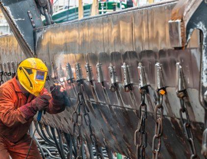 Lasser in IJmuiden last aan een schip. Nederland blijkt een van de meest productieve en concurrerende economiën ter wereld.
